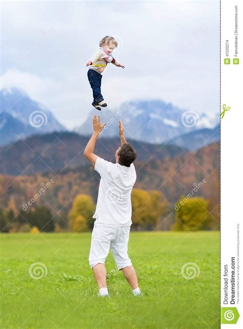 Young Father Throwing His Baby High In The Sky Stock Photo